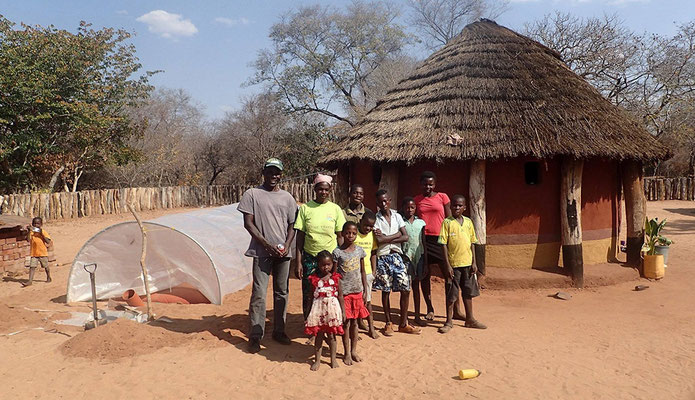 Village Head Douglas Ncube with his family next to their new biogas unit