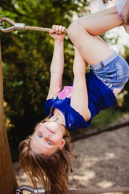 Mädchen baumelt am Klettergerüst