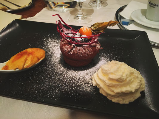 Dessert: Chocolate tart with soft centre served with spoon of creme brulee and semolina whipped cream