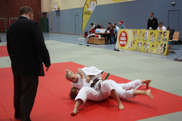 Chiara-Sue Pätzold hat ihre Gegnerin im Haltegriff unter den aufmerksamen Augen des Kampfrichters.