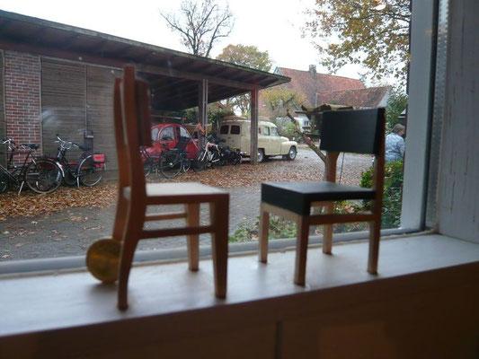 Stühle in der Werkstatt und der Fuhrpark auf dem Hof.