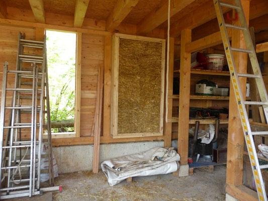 Rückwand der Scheune mit Lärchenholz und einem Lehmbau-Schauobjekt