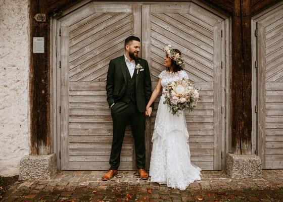 Boho Brautkleid, Boho Wedding, Brautpaar vor Scheunentor, professionelles Fotoshooting