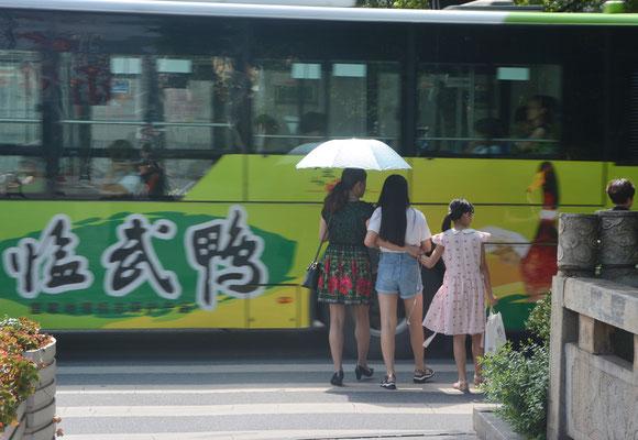 Une mère et ses filles attendent de pouvoir traverser la rue à Chenzhou (HUNAN) ©Michel AYMERICH