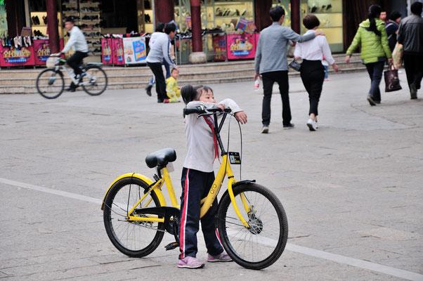 Petite fille pour un grand vélo dans le quartier des pagodes à Kunming (Yunnan), Chine 2017 ©AYMERICH Michel