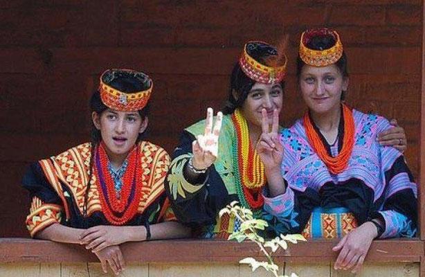 Trois jeunes filles Kalash font le signe de la victoire.