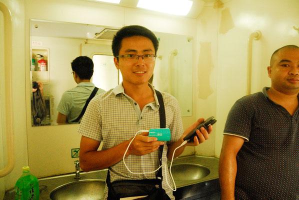 Dans le train nous conduisant de Guangzhou à Shangrao, Zhang Wei, mon guide, recharge mon Smartphone à l'aide de son chargeur transportable ©Michel AYMERICH