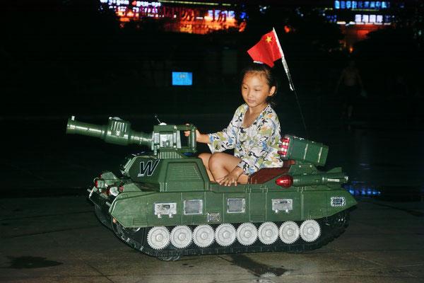 La nuit sur la place à Chenzhou (HUNAN). Des enfants jouent. L'armée populaire est intégrée dans le paysage mental des Chinois, bien plus que ne l'est l'armée française auprès des Français... ©Michel AYMERICH