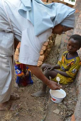 Sr Medhin che insegna al bambino come dare da mangiare al fratellino