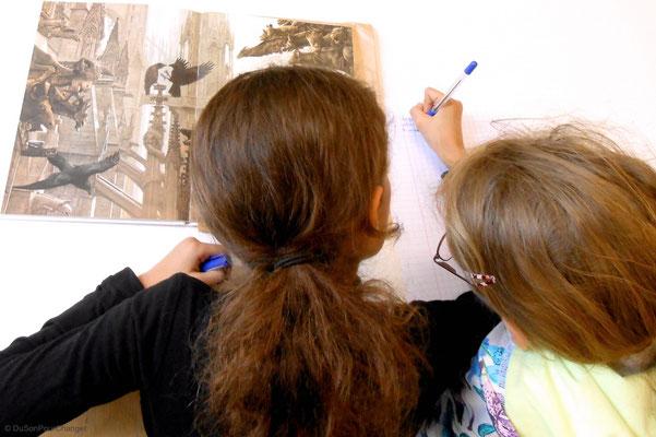Deux élèves listent des éléments observés dans le livre Cathédrale, de John Howe - paru à La Nuée Bleue
