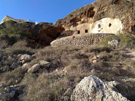 links oben ein moderner Neubau, über der Natursteinterrasse das alte Höhlenhaus