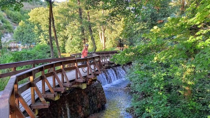 geschwungene Holfbrücke für Fußgänger und Radfahrer über den Fluß