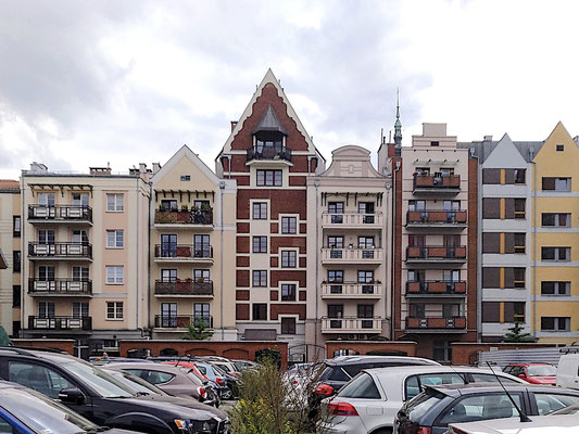 auf der Rückseite der Häuser haben die Bewohner ihre Balkone und darunter die Autos