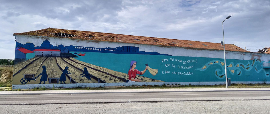 gegenüber eine Halle mit Wandmalerei über Fische verarbeitende Frauen