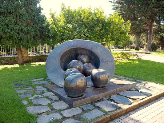 eine Skulptur, in der Äpfel aus einem Hut rollen