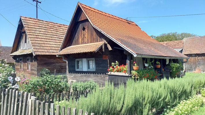 typische Holzhäuser, das Dorf Krapje zieht sich kilometerweit eine Straße entlang und besteht noch immer aus einer Vielzahl dieser Häuser