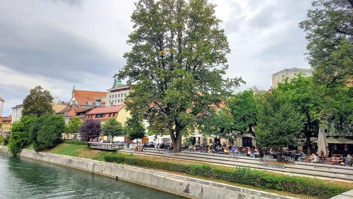 auf einer breiten Promenade reiht am Flussufer reiht sich ein Restaurant/Café ans andere