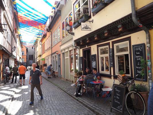 Wohnhäuser zu beiden Seiten mit kleinen Lokalen und Geschäften