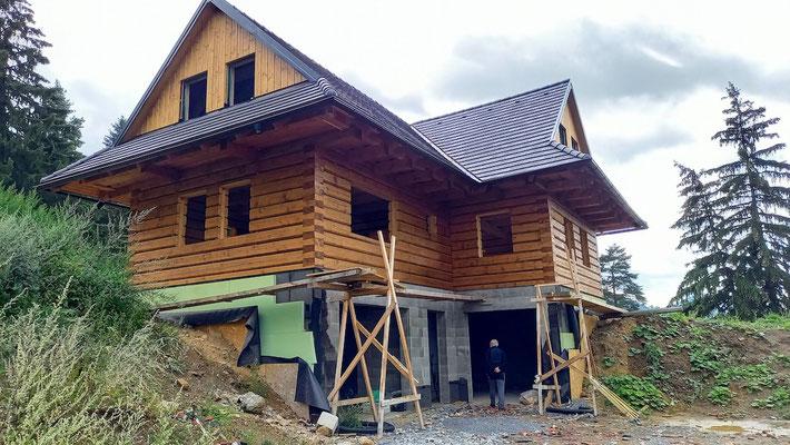 Gabriel schaut sich die dicke Isolierschicht an, die sich bei allen dieser anscheinend hochwertigen Holzhäuser findet