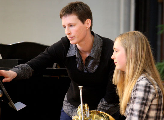 Christine Passmore of True North Brass works with a French horn student during open coaching at the Brass Festival.