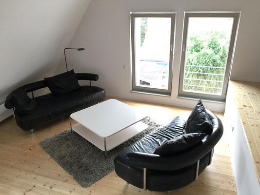 Wohnzimmer im Dachgeschoss mit gemütlichen Sofas