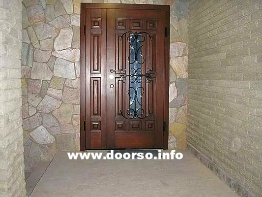 Филенчатая металлическая дверь со стеклом и оригинальной ковкой.