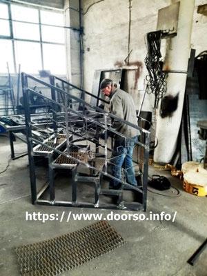 Сварка металлического крыльца происходит в цеху.