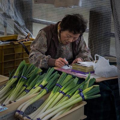 Una signora vende porri a Takayama