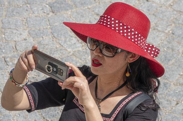 rote Hüte und Handy; Foto: Ernst Ostertag