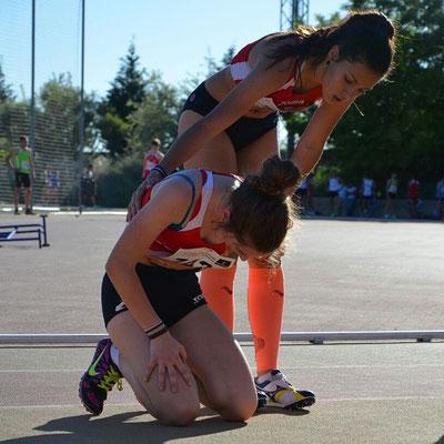 Carolina de rodillas ayudada por su compañera de entrenamiento María Laguna