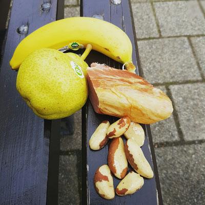 Mittagessen auf einer Parkbank (geräucherte Schweinelende, Birne, Banane, Nüsse)