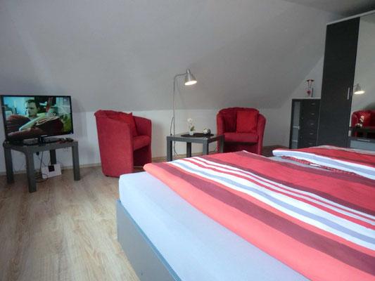 Das rote Schlafzimmer mit gemütlicher Sitzgelegenheit und TV