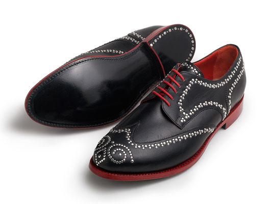 Fullbrogue Derby (Budapester), Obermaterial Schwarzes Leder mit Ziernieten, rahmengenäht mit schwarzer Ledersohle, rotes Futter und roter Schnitt, genagelte Lederabsätze