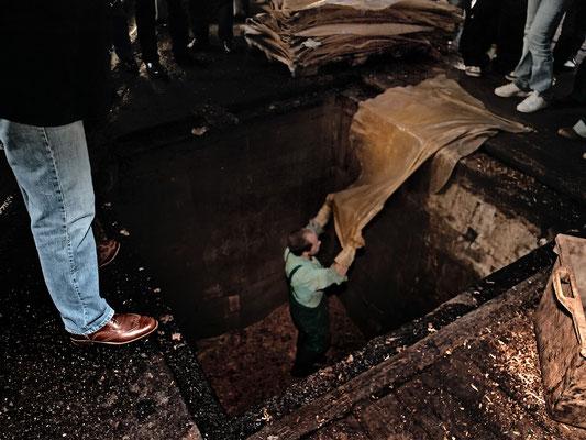 Eine Gerbgrube wird von Hand mit Lohe und Häuten gefüllt. Schicht für Schicht.