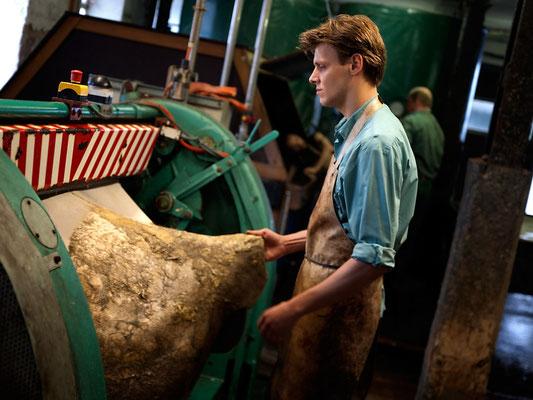 Entfleischen Auf der Entfleischmaschine wird die zuvor im Äscher gequollene Haut mit Hilfe eines Messerzylinders bei 1.800 Umdrehungen pro Minute von Fett und Fleisch befreit.