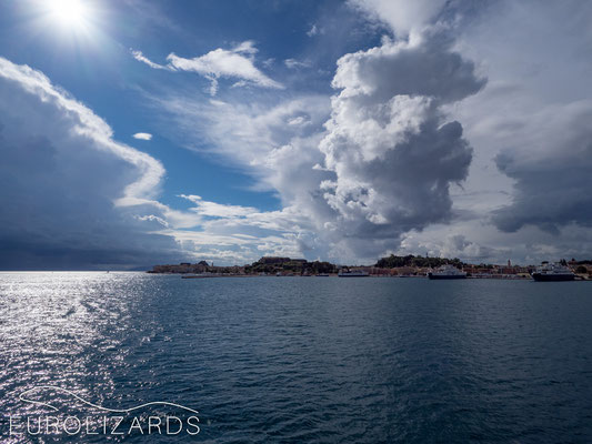 Leaving Corfu: Sun over the sea and clouds in the mountains