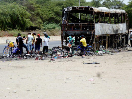 Scrounging through the wreckage. The bus was set on fire the previous day.
