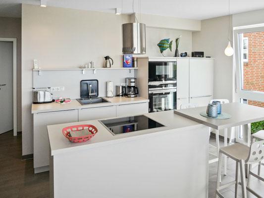 Die Küchenzeile mit einer zusätzlichen frei stehenden Kücheninsel (mit Induktionskochfeldern) ist komplett ausgestattet.