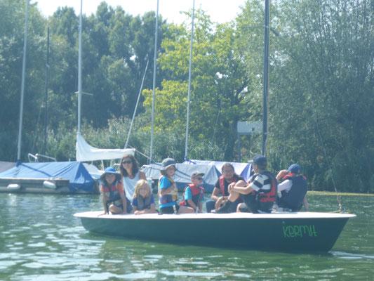 Kinder beobachten die Regatta vom Segelboot aus