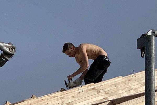 Blockhaus Bauen im Februar bei plus 20°C - Blockhausbauer - Winterbau - Blockhausbau - Handwerker auf dem Dach