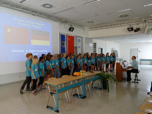 Zur Begrüßung sang der Mittelstufenchor der Kopernikusschule unter der Leitung von Hr. Zellmann für die Gäste. Klick auf das Foto um den Film zu sehen!