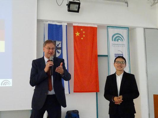 Schulleiter Hr. Mayer, selbst China-erfahren, begrüßte die chinesischen Gäste. Fr. Pu-Kleene, Chinesischlehrerin an der KSF und Organisatorin des schulübergreifenden Austauschprogrammes, übersetzt.