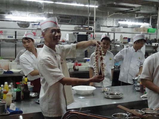 Köche präsentieren den vorbereiteten Fisch vor dem Frittieren.