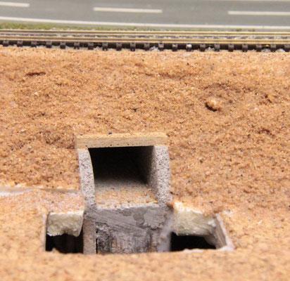 04.08.2012   Nach dem Fixieren des Durchlaßtunnels an seiner korrekten Stelle, wird der Bahndamm mit Sand und Leim an den Tunnelausgang angeglichen.