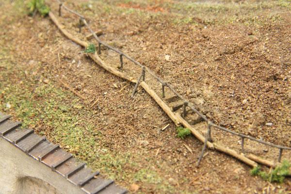 01.10.2013  Einige Stufenbretter aus gebeiztem Furnier ergänzen das Bild. Zur Abfangung des Weges wurden auf der Bergabseite Rundhölzer mit Eisenstäben platziert.