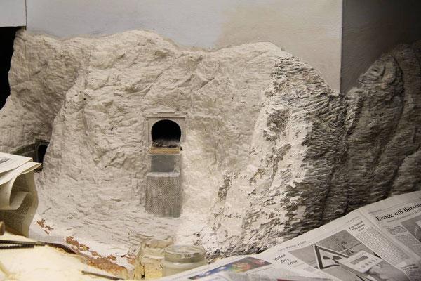 20.03.2011   Er dient als Auflage für das eine Ende des Viaduktmodellles. Der Anschluß der neuen Felswand an die farblich schon fertig gestalteten Felsen erweist sich als schwierig. Deshalb wird ein Teil des fertigen Felsens nochmals überarbeitet.