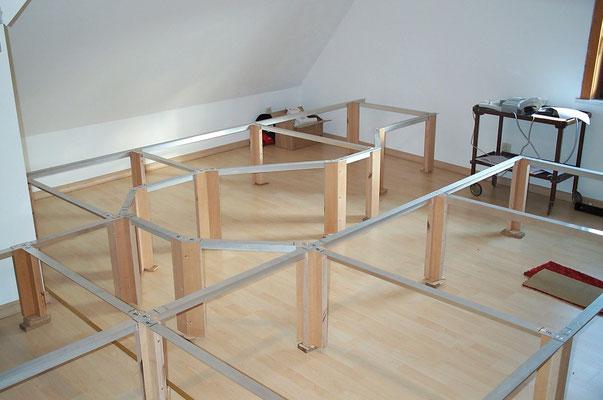 25.08.2007   Da der Fußboden der Dachkammer weder eben noch waagrecht ist, wurden die Anlagenbeine mit Hölzern unterbaut bis die Alu-Profile in der exakten Waagrechten lagen. Mit einem gleichmäßig breitem Holzstück wurde die untere Schnittkante angerissen