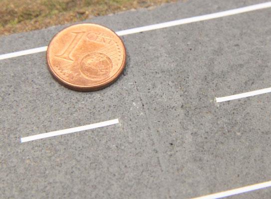27.09.2012    Die Straßenmarkierung ergänzt den Fahrbahnbelag. Erkennbarer Querstoß des Straßenbelages.