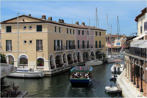 """Un """"coche d""""eau"""" électrique passe sur le canal. Vue depuis le pont."""