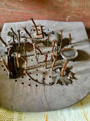 Aktion: Die Sitzfläche eines alten Stuhles wurde mit handgeschmiedeten Nägeln gespickt
